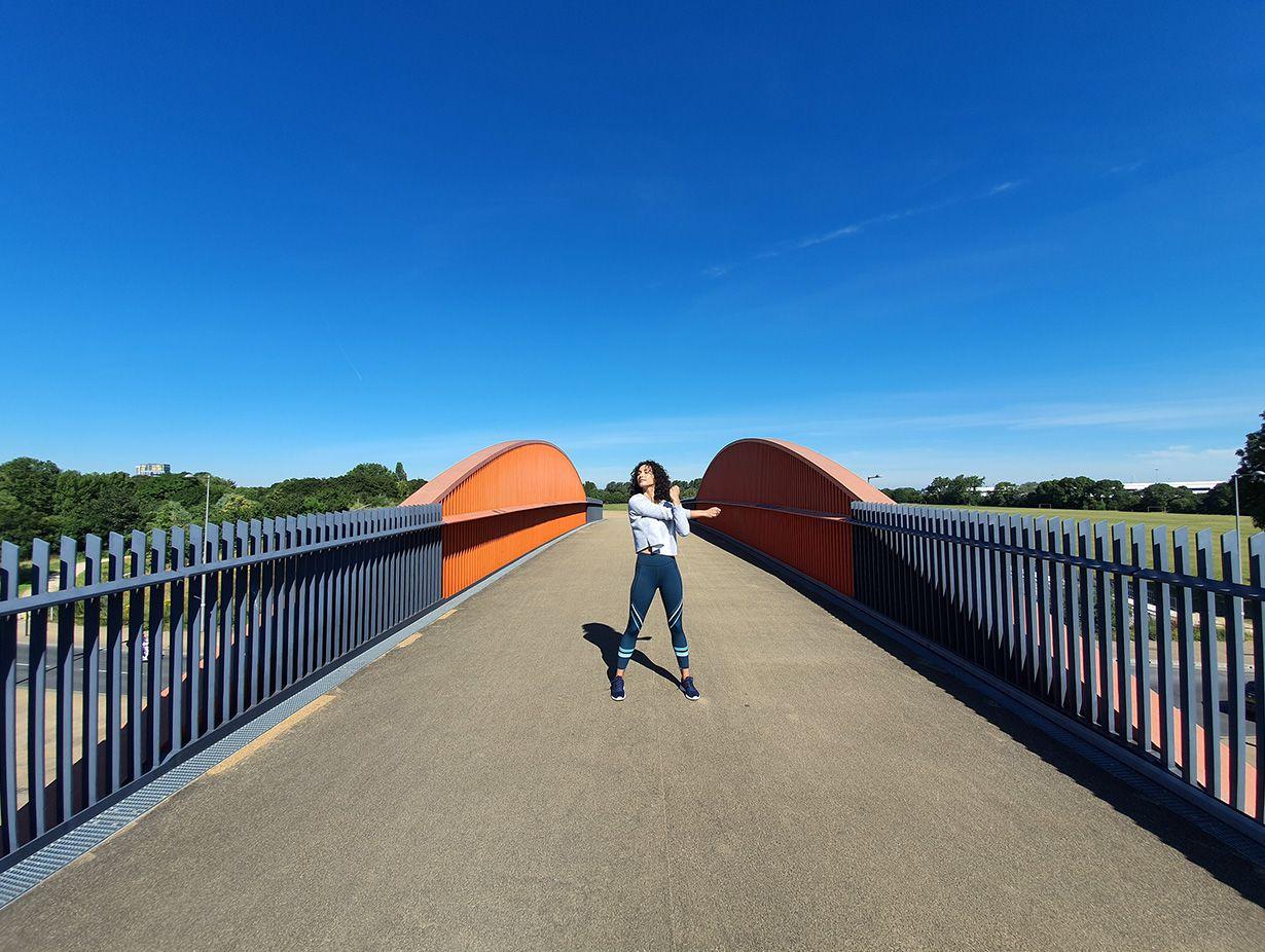 Photo prise par l'appareil photo ultra large d'une femme qui s'étend sur un pont avec des portes grises et des accents orange sur un ciel bleu vif