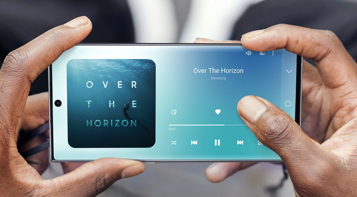 Hands holding Galaxy Note10 plus in landscape mode with Samsung Music onscreen playing a song. Illustrated rings pulse out from the phone to represent the stereo audio enhanced by Dolby Atmos for a 3D immersive sound experience