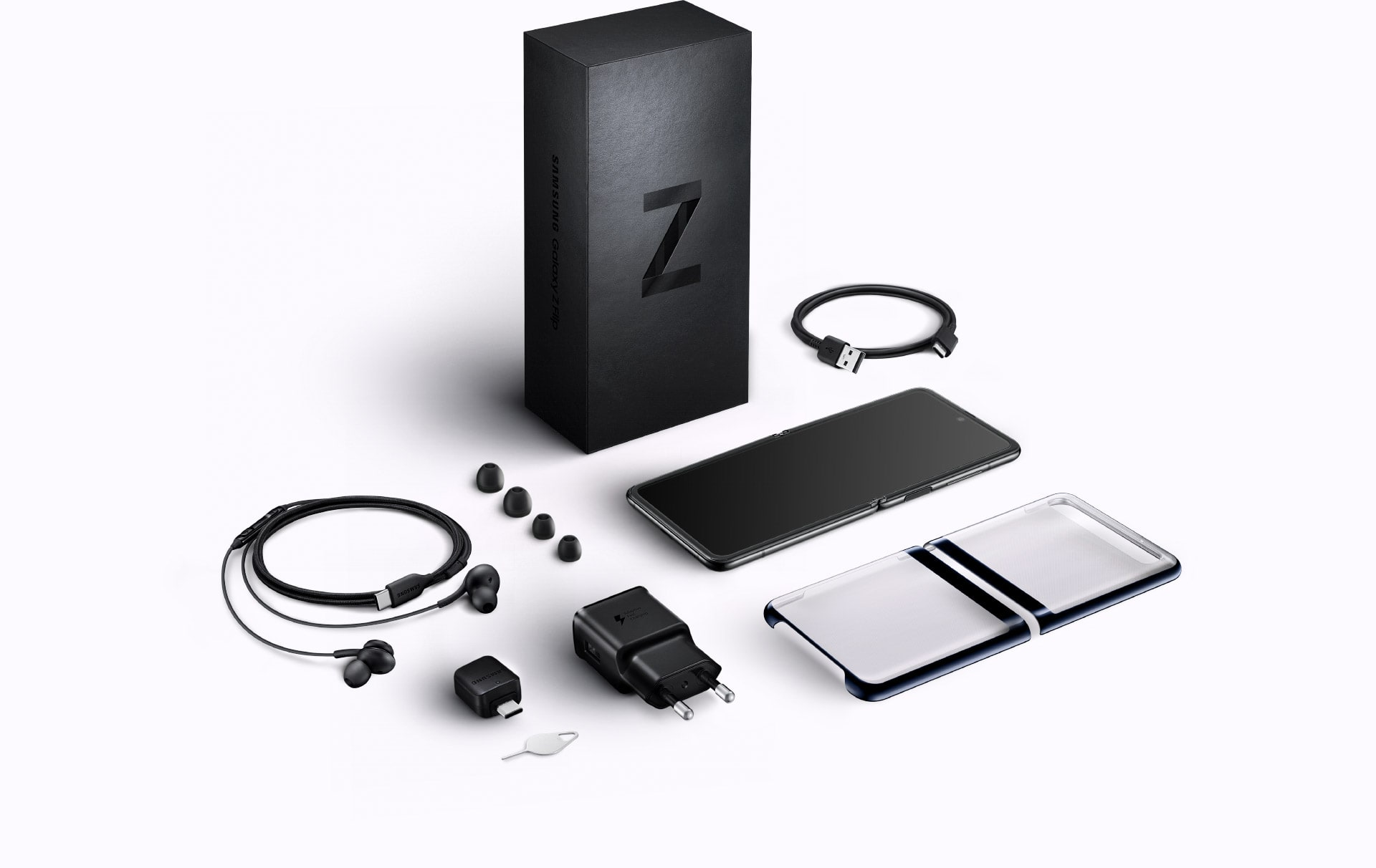 A flat lay of the items included in box with Galaxy Z Flip. The packaging, the device, a Clear Cover, the USB Type-C cable, travel adapter, headphones, earbud tips, and a SIM tray ejector