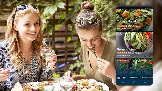 Two women eating salads in a restaurant and a screen showing that Bixby provides information about the restaurant selling salads by learning routines.