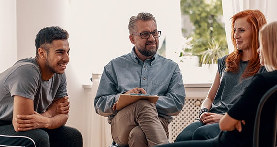 An image of a woman and two men interviewing her.