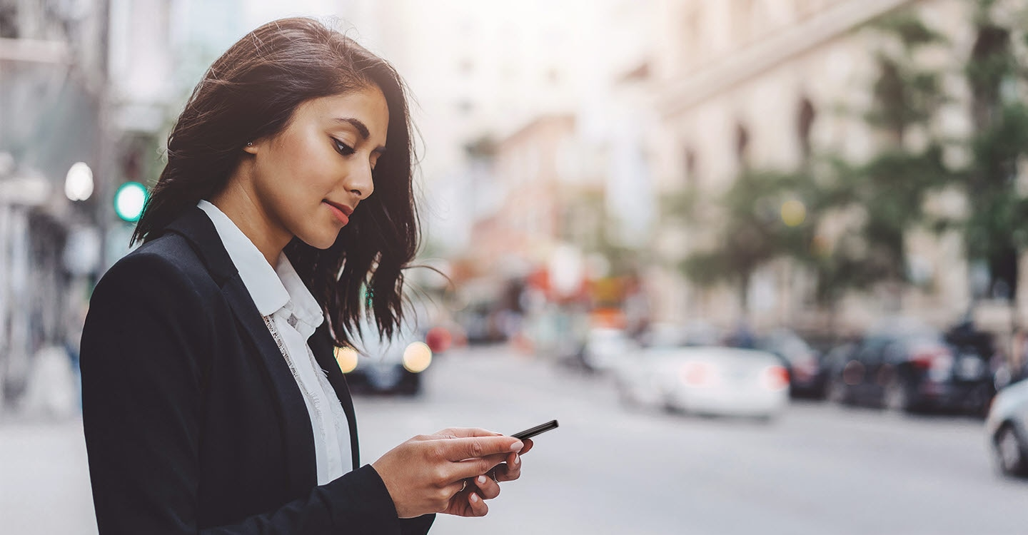 An image of a woman looking at her cellphone in the street.