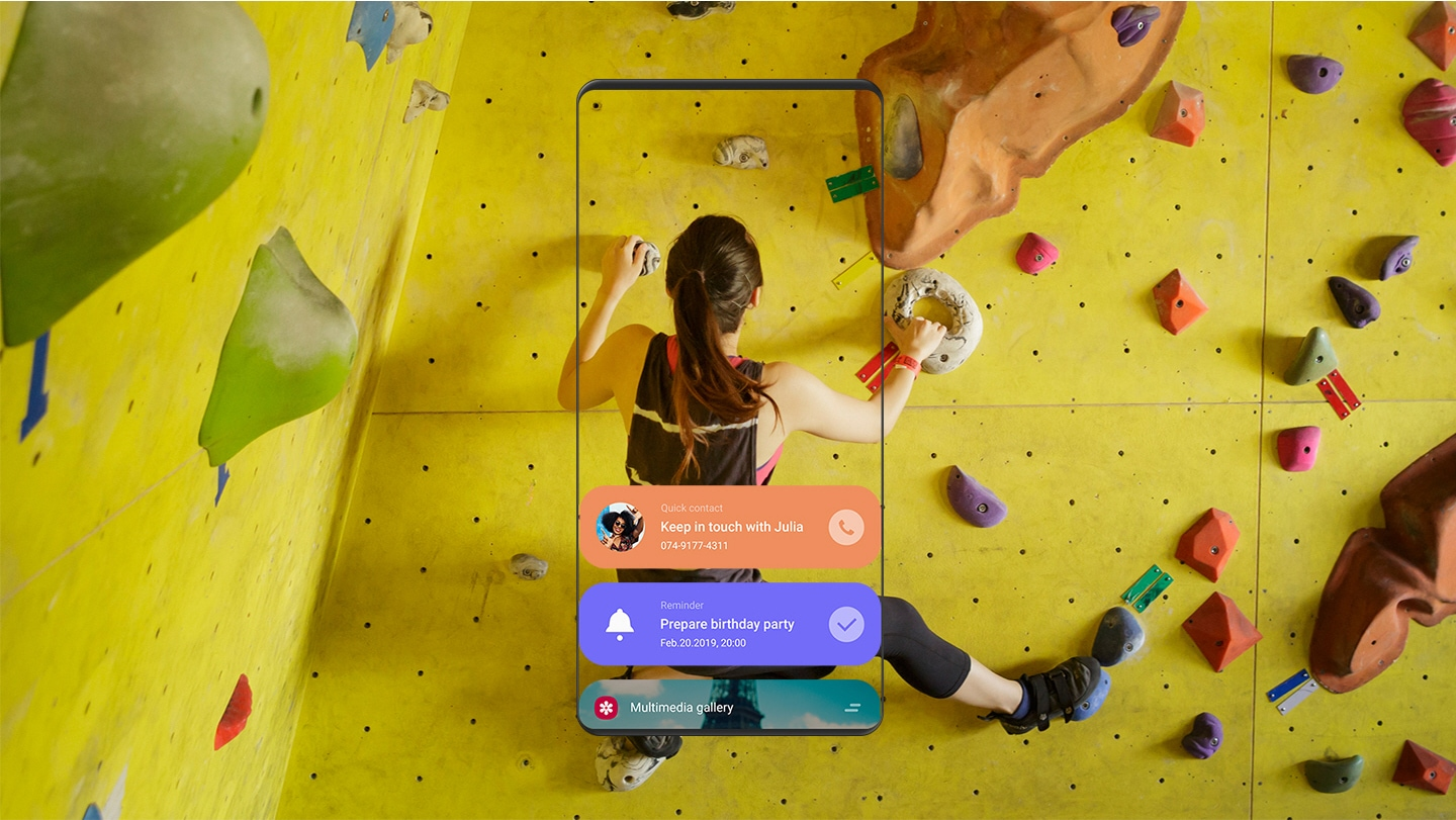 An image showing a woman doing indoor rock climbing and a front view of a smartphone showing Quick contact, Reminder, Multimedia gallery apps running on Bixby Home.