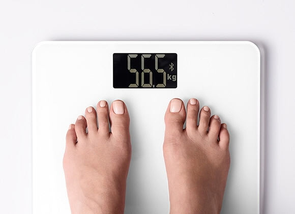 The feet on a set of scales showing the user's weight.