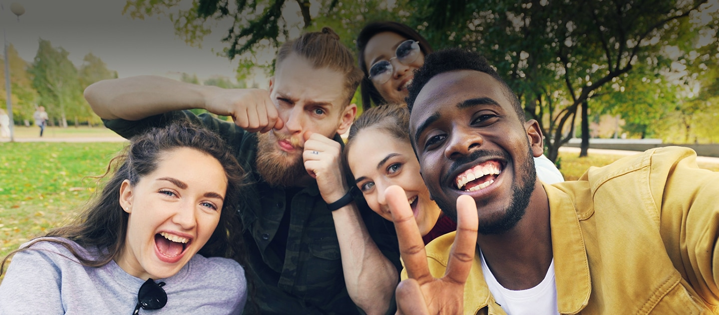 Five people smiling and taking a selfie together in a Park.