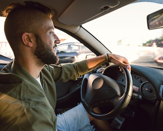 A man using Bixby Quick Commands while driving a car. Bixby's Quick Commands GUI is in 'Going Home' mode.