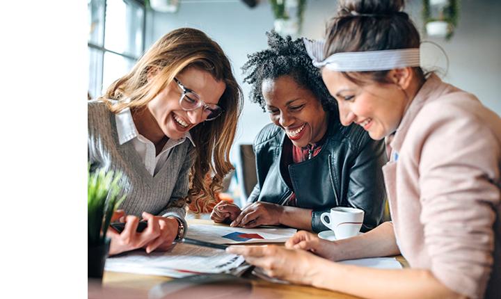 三個女人坐在桌子旁笑著一起工作。