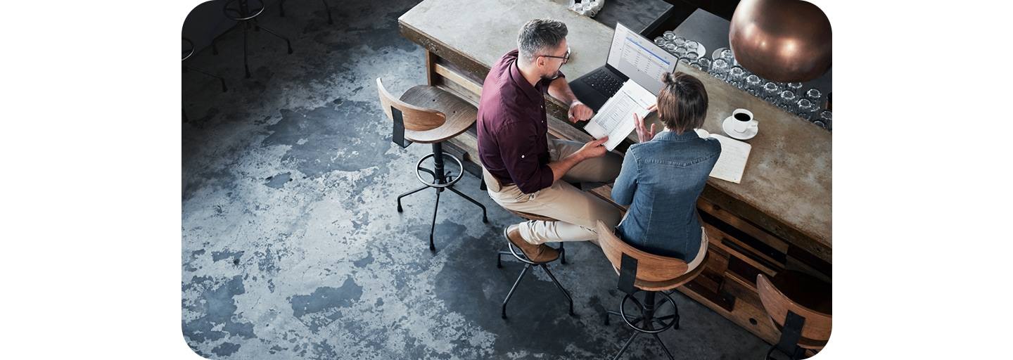 Two people sitting at the bar of a coffee shop, looking at papers and a laptop