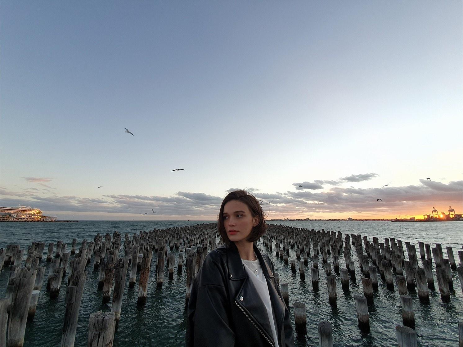 Снимка на жена, която стои пред няколко дървени стълба в морето на здрачаване, заснета с Galaxy S10 plus. Изтегля се, за да се покаже по-голяма част от пейзажа с ултраширокоъгълната камера.