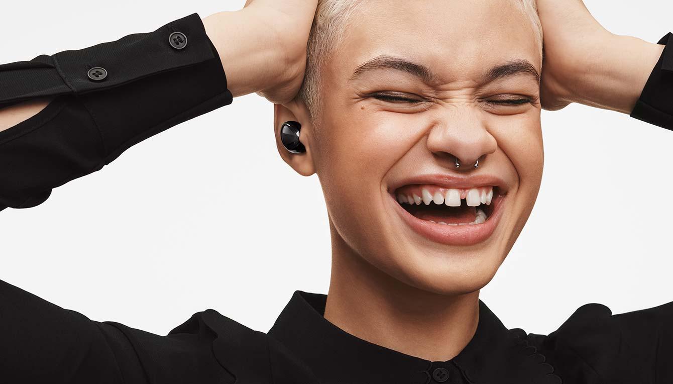 Un primer plano de una oreja con Galaxy Buds Pro dentro. Se aleja para mostrar a una mujer que lleva los auriculares puestos, con una amplia sonrisa.