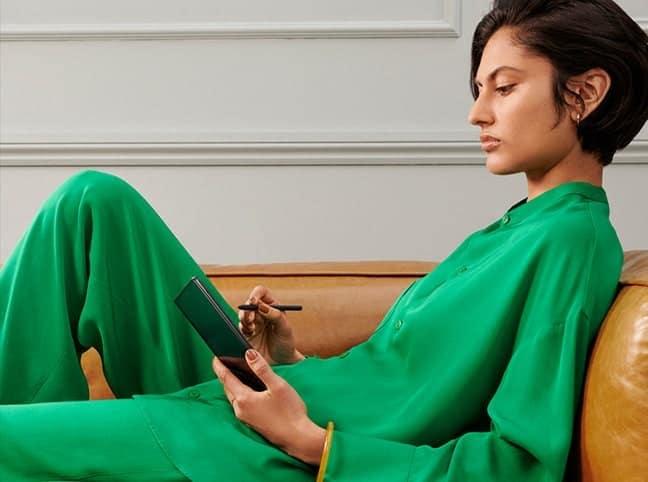 Žena lenoší na gauči a skicuje s perem S Pen na rozloženém Galaxy Z Fold3 5G.