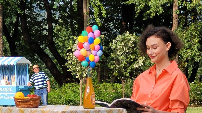 Photo zoomée 10x, se rapprochant encore plus de la femme assise seule à une table. Plus de détails apparaissent: elle lit un magazine et de nombreux mini ballons et une bouteille orange sont posés sur la table.