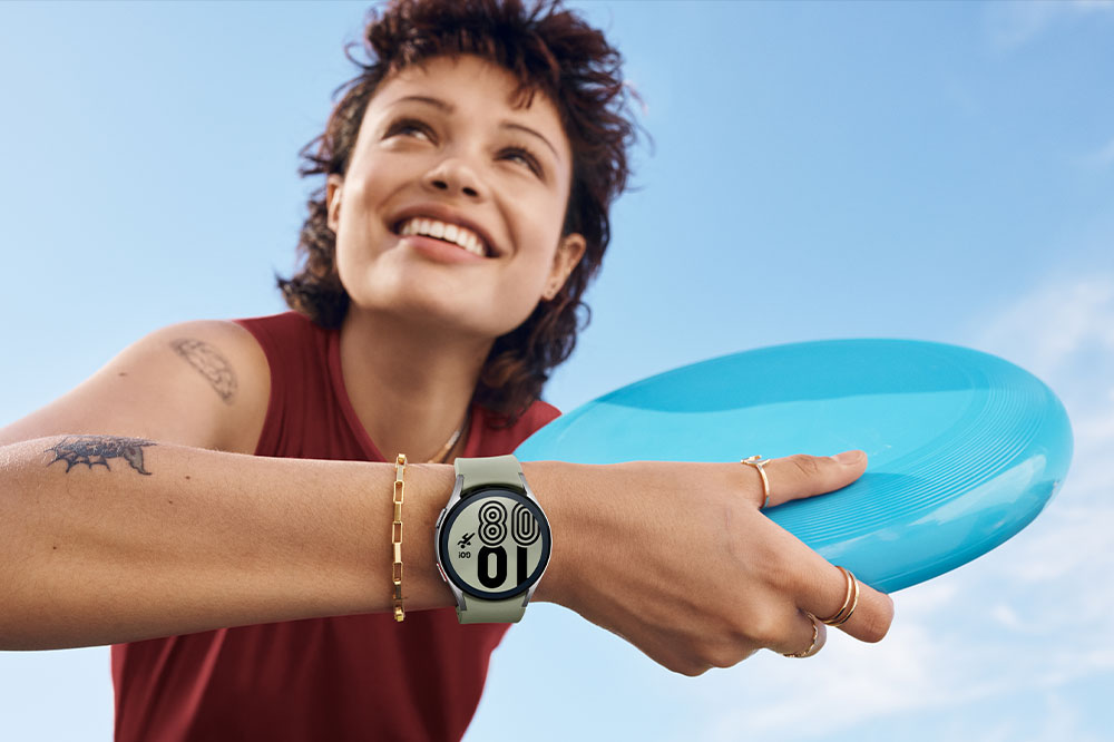 A woman is smiling and holding a frisbee while wearing a silver Galaxy Watch4 on her wrist.