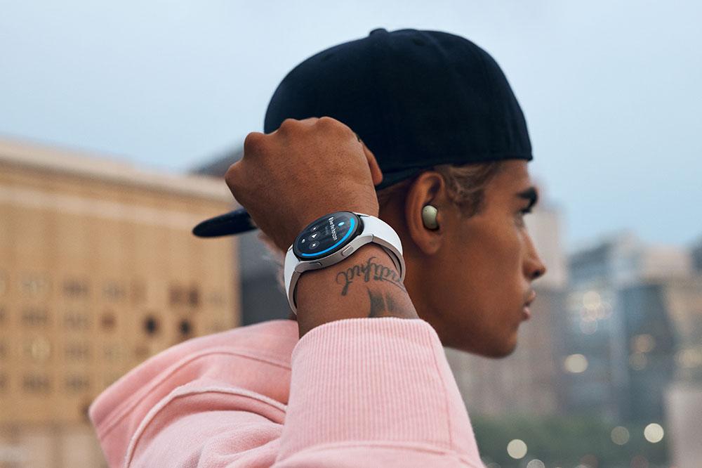 Muškarac sa šiltericom okrenutom naopako nosi Galaxy Buds2 slušalice i Galaxy Watch4 Classic uređaj. Desna mu je ruka, na kojoj se nalazi sat, podignuta te muškarac gleda u gradski krajolik u daljini.