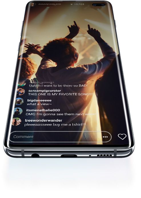 Galaxy S10 plus laying on its back, seen at a slight angle from below. It starts with a prismatic S10 logo graphic onscreen. This shifts to a prismatic Wi-Fi icon, then shifts once more to a livestreamed concert with comments overlaid onscreen.