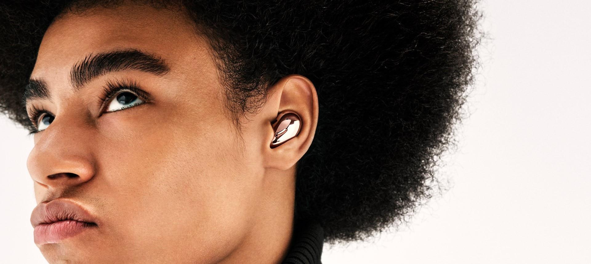 Vue partielle d'un homme avec une coupe afro portant des Galaxy Buds Live Bronze Mystique. La caméra effectue un zoom avant pour faire un gros plan sur son oreille.