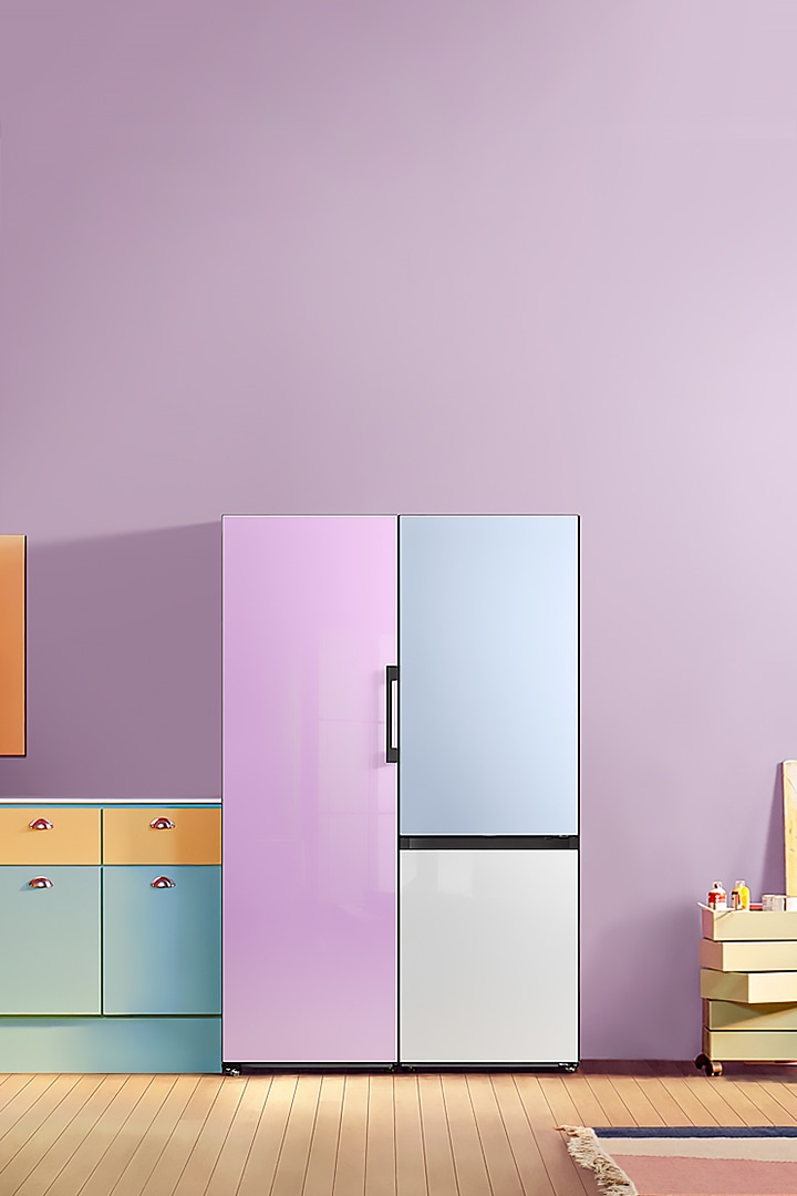 A Glam Lavender 1-door Bespoke refrigerator and a 2-door unit with a Satin Sky Blue top panel and a Clean White bottom panel are placed side-by-side in a colorful kitchen.