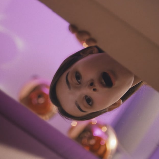 A girl peers down into a box with a surprised expression.
