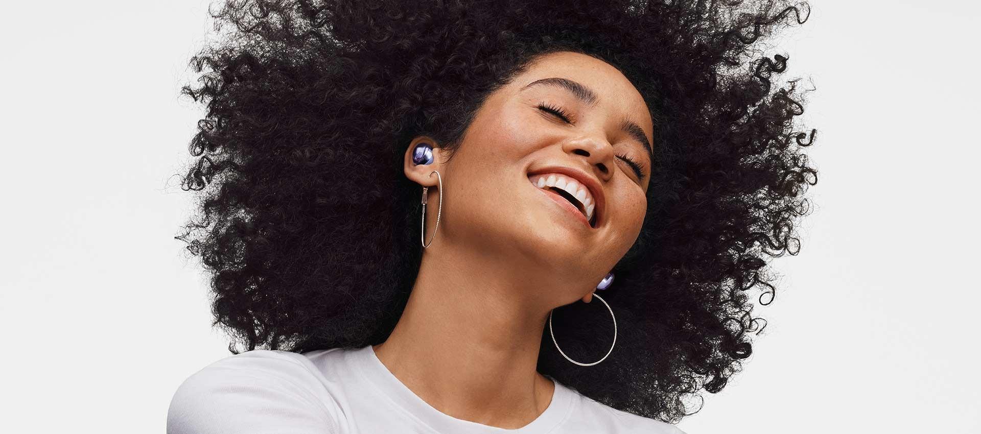 Una mujer sonríe inclinando su cabeza hacia atrás mientras usa los Galaxy Buds Pro.