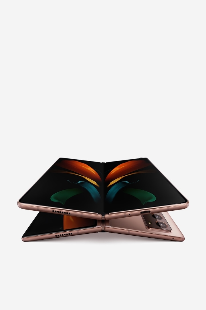 Two unfolded Galaxy Z Fold2 phones in Mystic Bronze, one laying face up and the other laying facedown. The one seen from the front is on top of the one seen laying facedown and has the butterfly wallpaper onscreen.