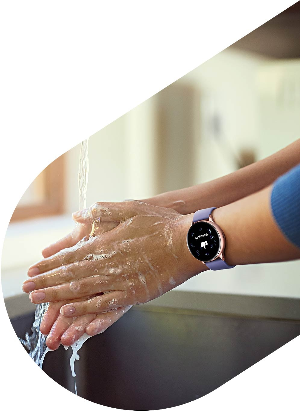 A person washes their hands while wearing the Rose Gold Galaxy Watch Active2.