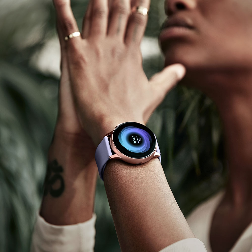Woman practices yoga with hands in prayer pose while wearing Rose Gold Galaxy Watch Active2. The watch face displays breathing exercises.