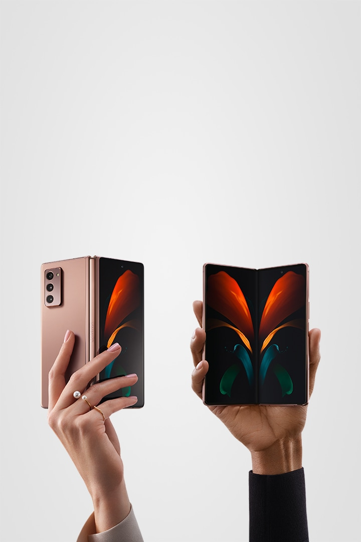 Two hands holding a Galaxy Z Fold2 5G phone. One is seen from the rear slightly folded, and the other is seen from the front slightly folded.