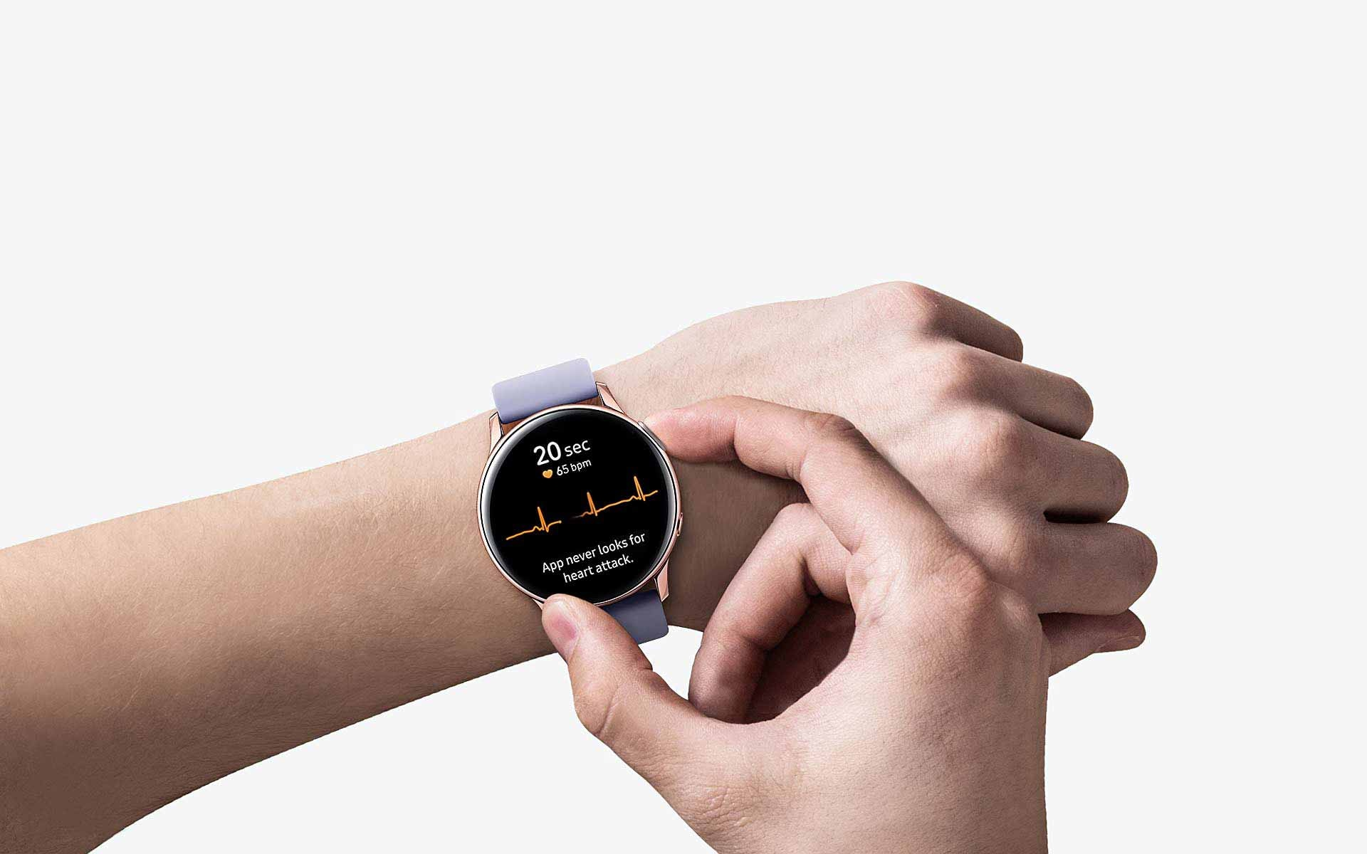 A person wears the Black Galaxy Watch Active2 with only their arms showing. A hand presses a button on the watch's side, and ECG measurements are shown on the watch face.