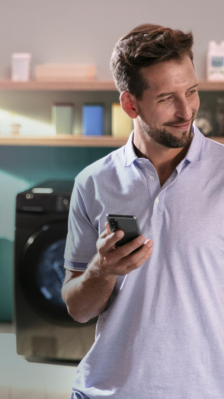 Man holding phone in laundry room