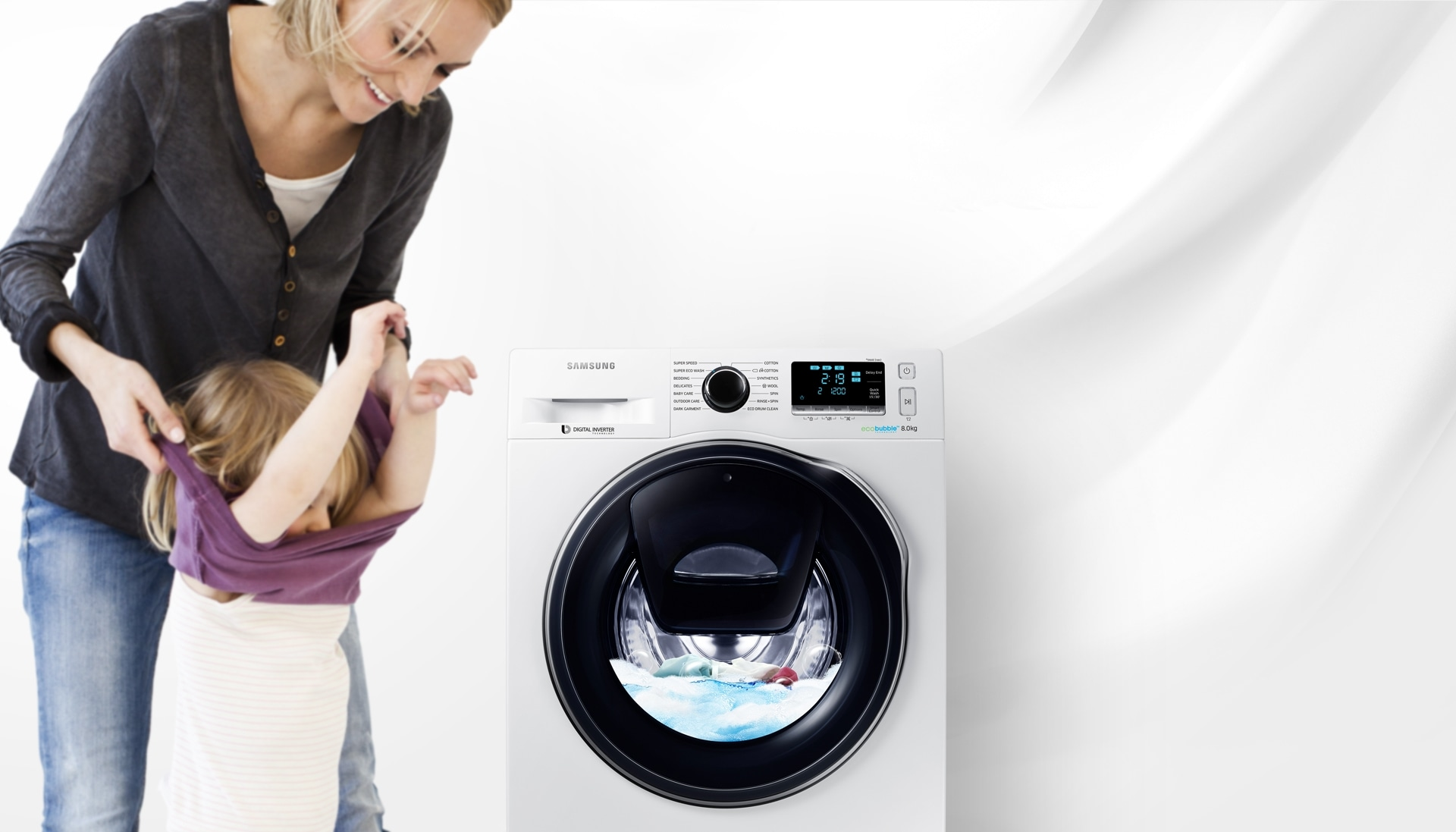 An image of a woman taking off her child's clothes next to a WW7500 washing machine which is in the middle of a cycle.