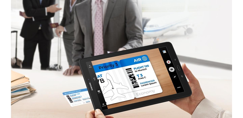 Mão masculina segura o Samsung Galaxy Tab na horizontal com imagem fotografada de uma passagem aérea que está sobre a mesa. Ao fundo, homens engravatados, segurando malas de viagem