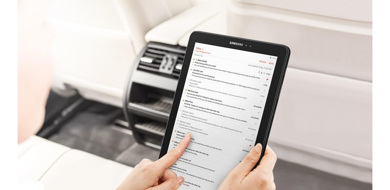 Mão feminina segura o Samsung Galaxy Tab A com informações na tela e imagem desfocada ao fundo de uma impressora