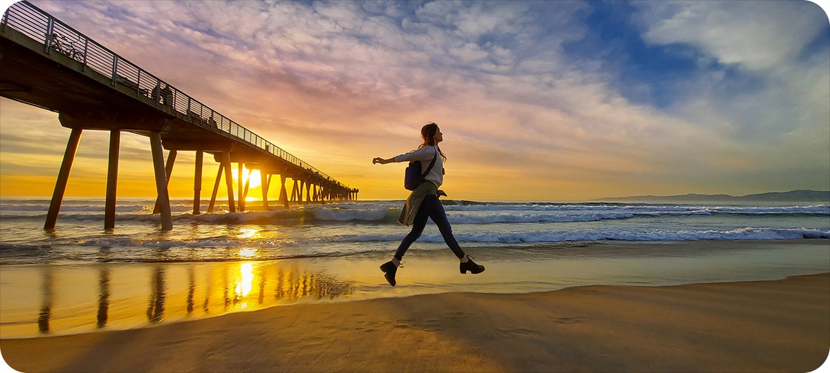 Image of young women jumping to strike a pose on a beach with ocean waves and pier in the background and sunset moodlighting in the horizon.