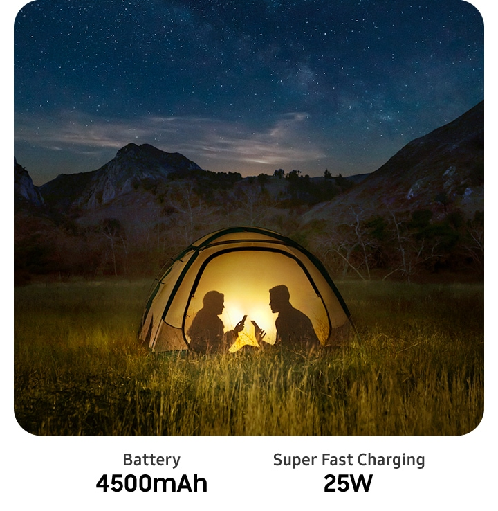 Silhouette of couple sitting in a tent in the middle of the night holding Galaxy A71 phones while bright screens illuminate the tent.