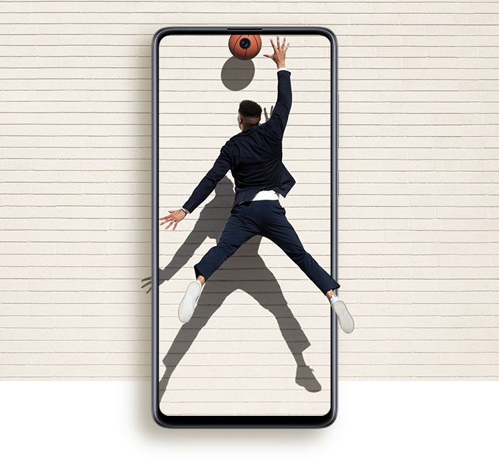 A man seen from behind jumping up with his right hand extended to grab a basketball. The basketball is centered on the front camera punch hole highlighting the Infinity-O Display design.