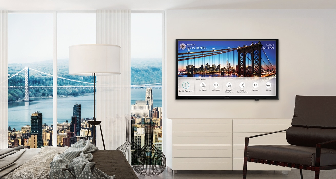 An image showing a Samsung hospitality TV installed on the wall in a hotel room with a bed and a chair. The TV screen displays the hotel information page.