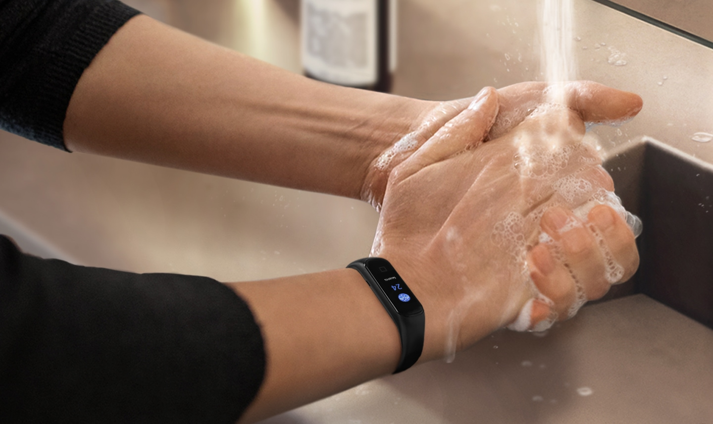 You can see a close-up of a person washing their hands with a black Galaxy Fit2 on their wrist that shows a countdown.