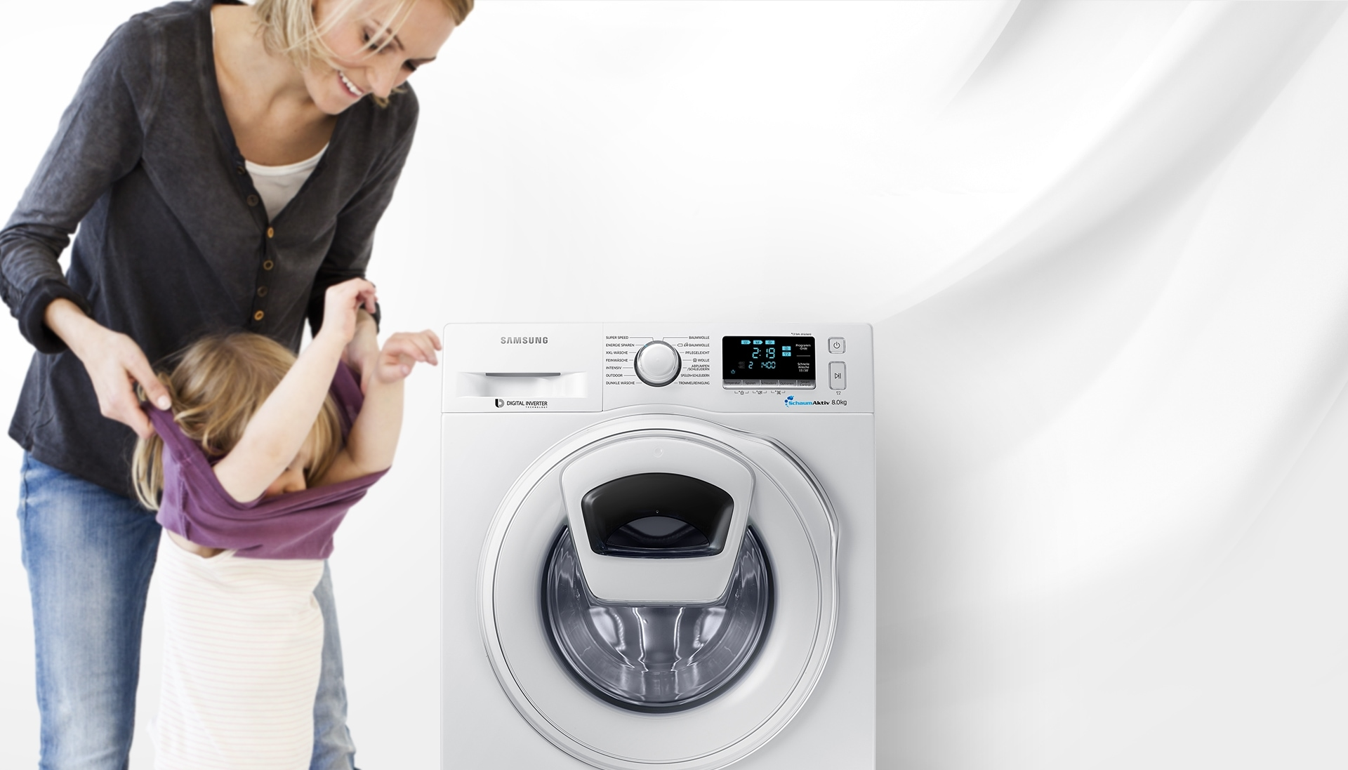 An image of a woman taking off her child's clothes next to a WW6500 washing machine which is in the middle of a cycle.