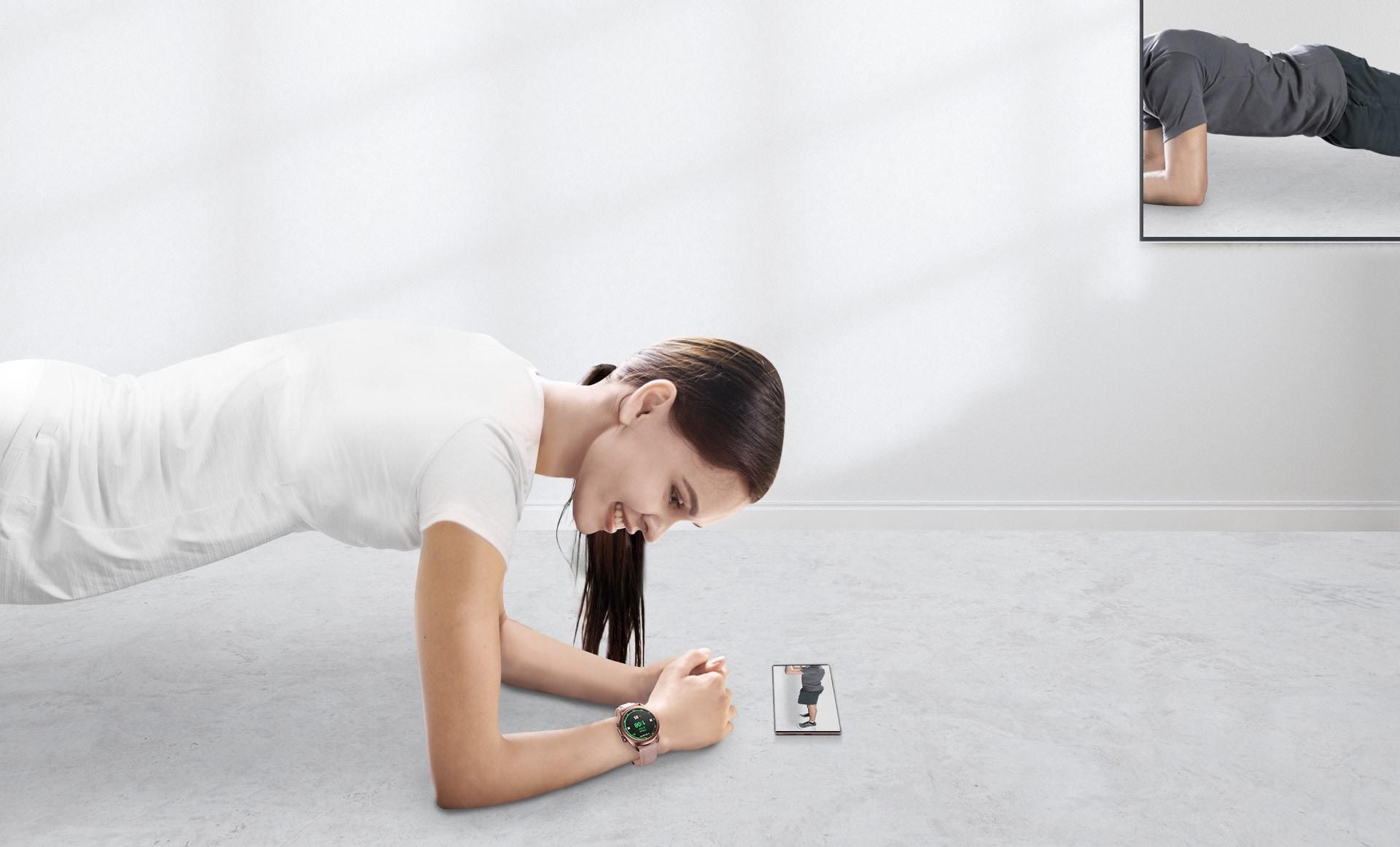 Une femme en position de planche suit un programme d'entraînement à domicile qui est diffusé depuis un smartphone Galaxy sur le téléviseur. La Galaxy Watch3 45 mm en Mystic Bronze est connectée pour mesurer sa fréquence cardiaque.