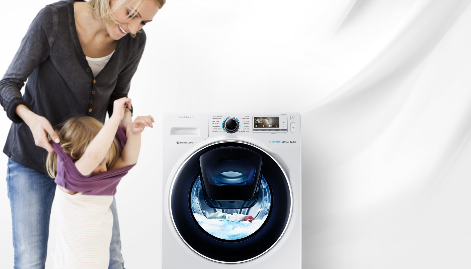 An image of a woman taking off her child's clothes next to a WW8500 washing machine which is in the middle of a cycle.