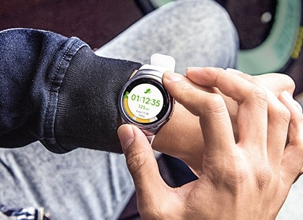 An image of a man checking out information on the S Health app by turning the silver Gear S2's rotating bezel.