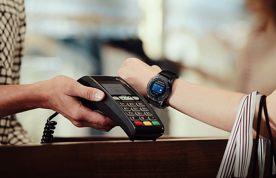 Woman extending wrist out to mst card payment machine to pay with Samsung Pay on her Gear S3