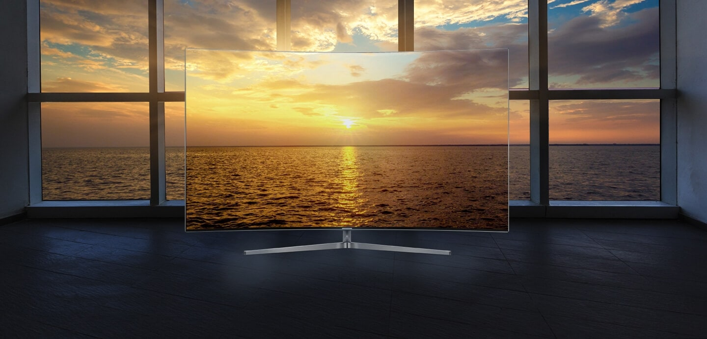Boundless screen of Samsung TV is standing in front of large window - night time view