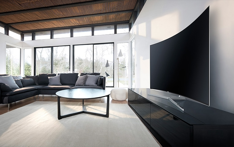 see large image of left perspective image of TV in a living room and round table is in front.