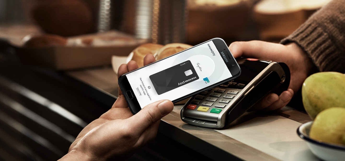 Image displays the Galaxy A7 (2017) completing a transaction with Samsung Pay.