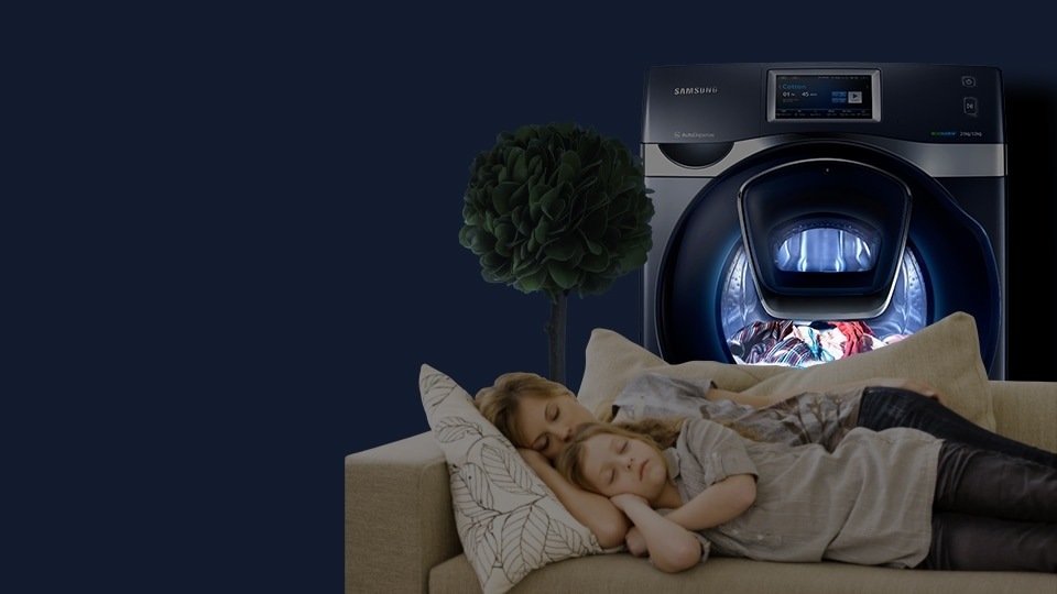 An image showing the WD9500K Add Wash operating, while two children sleep on a sofa in front of the machine.
