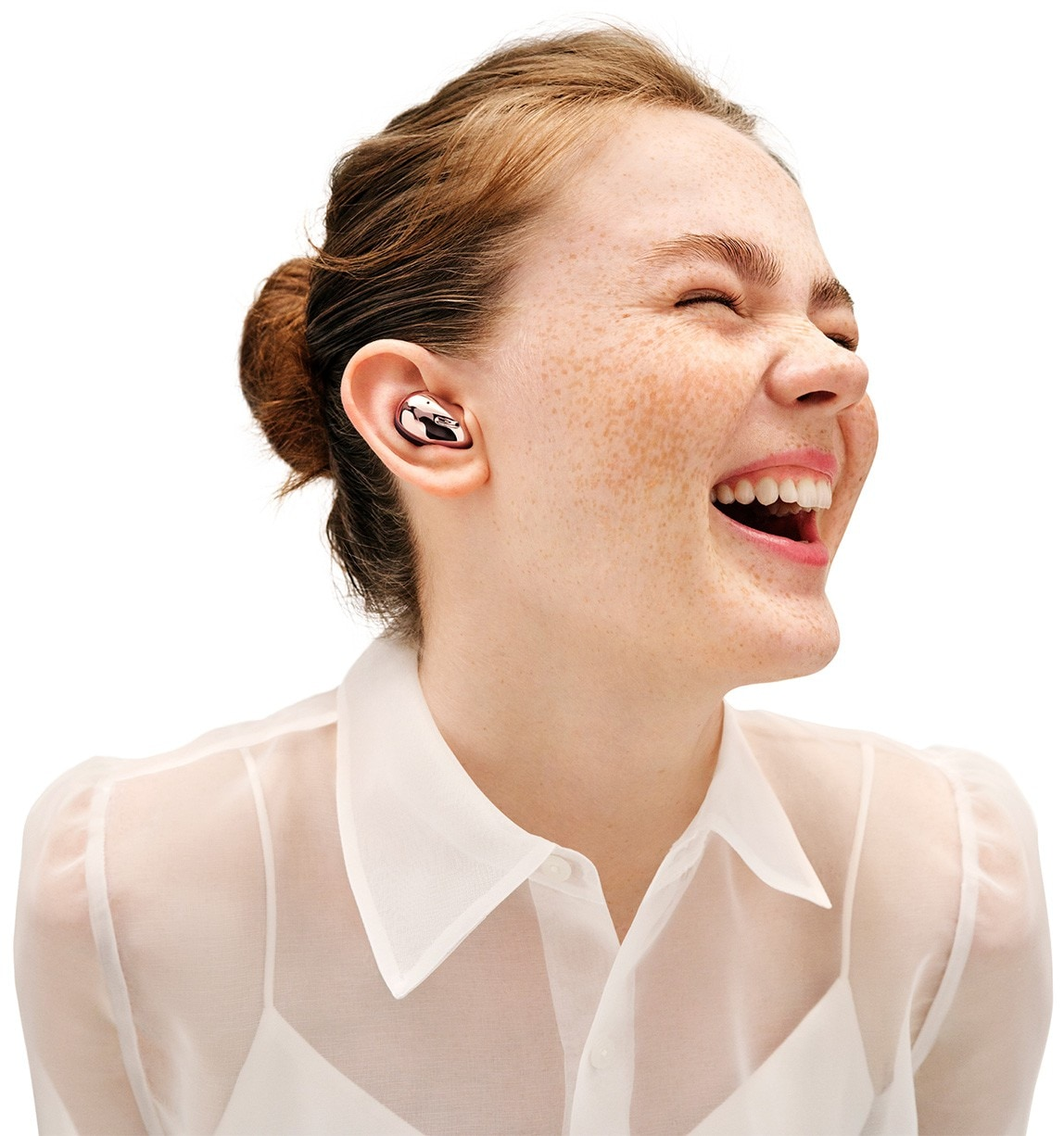 Front view of Galaxy Buds Live in Mystic Bronze. Right Galaxy Buds Live earbud disappears as the left earbud shrinks and fits in the ear of a woman laughing.
