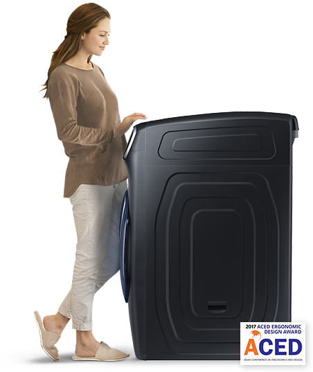 A woman stands by the washing machine. She appears to be loading laundry.