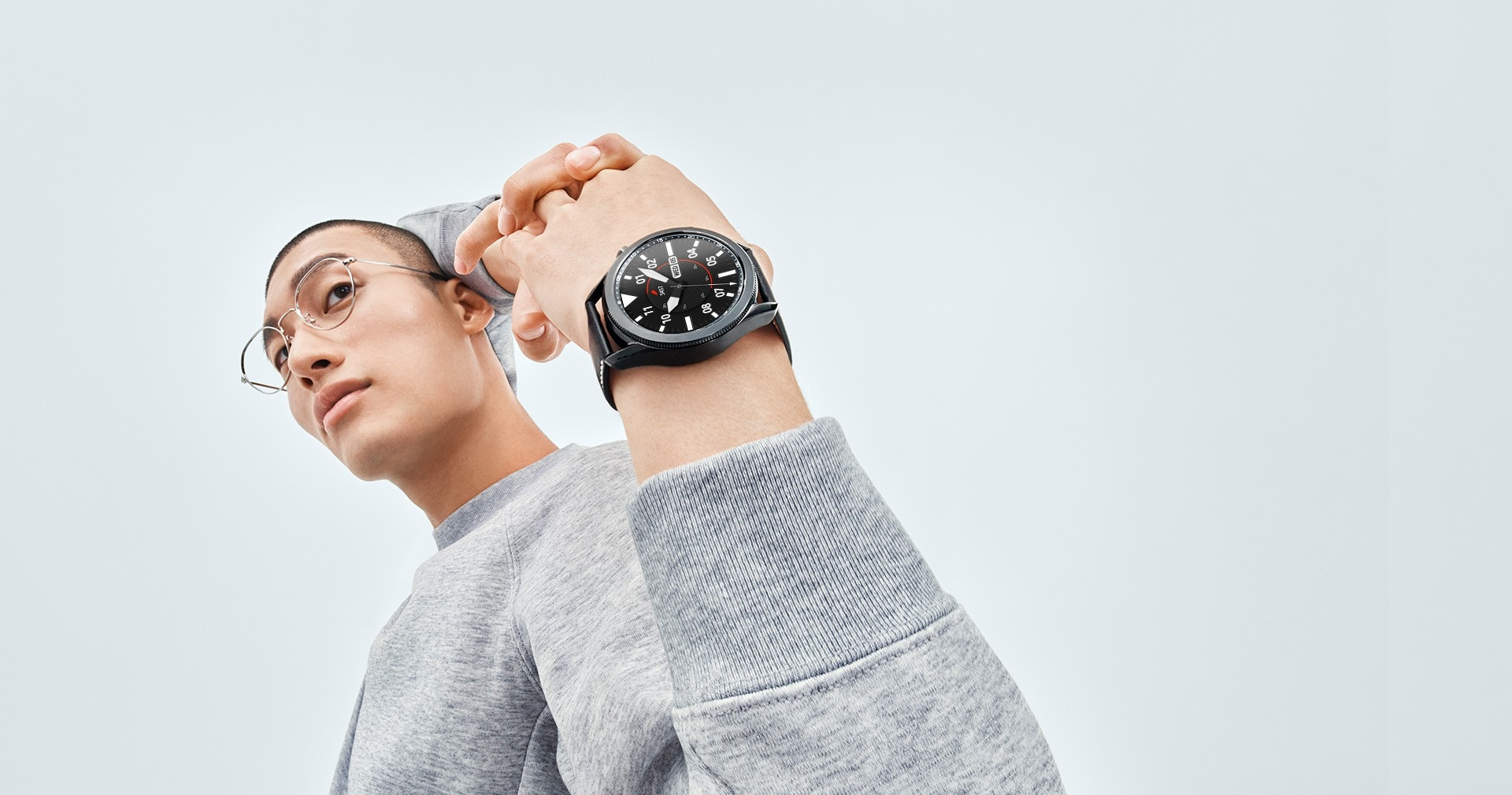 Man stretches his arms behind his back, showing off a 45mm Galaxy Watch3 in Mystic Black on his wrist with a Sporty Classic Watch Face.