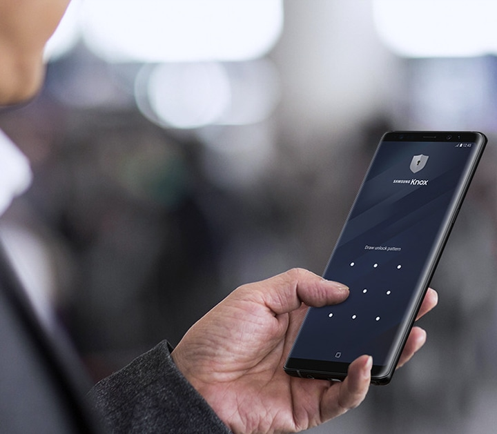 A man tapping on his Samsung smartphone with screen secured by Samsung Knox solution